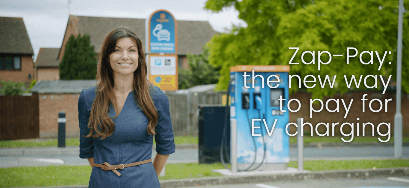 A woman standing in front of an Electric Vehicle charger.